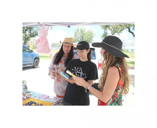 Market vendors Norma Castillo (left) and her daughter, Nicole Castillo (center) show Bandera Brewery event manager Elisabeth Cox their wares at last Saturday's Second Saturday Flea Market. The duo's homemade offerings included key chains, resin art, b